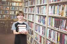 Smiling boy carrying a stack of books in a library.