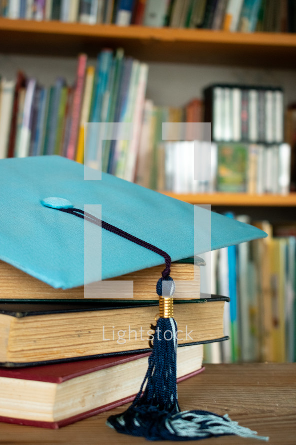 graduation cap on a stack of books on a desk