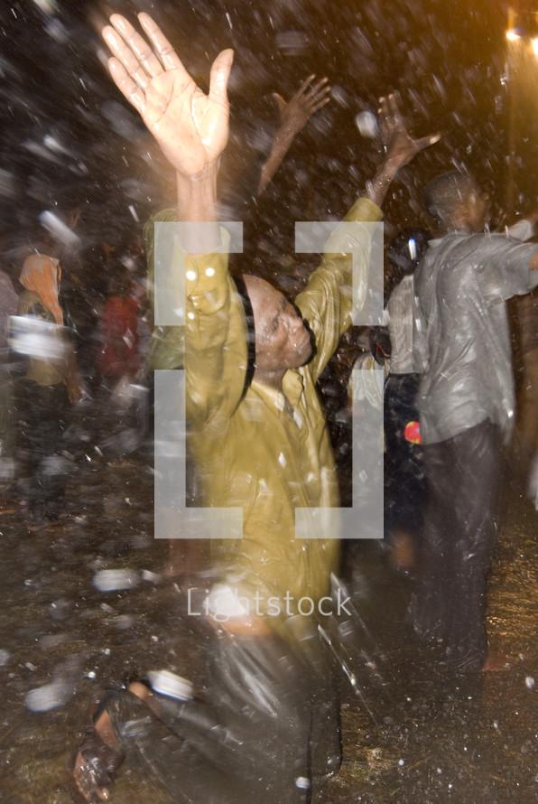 African man worshiping through a rain storm