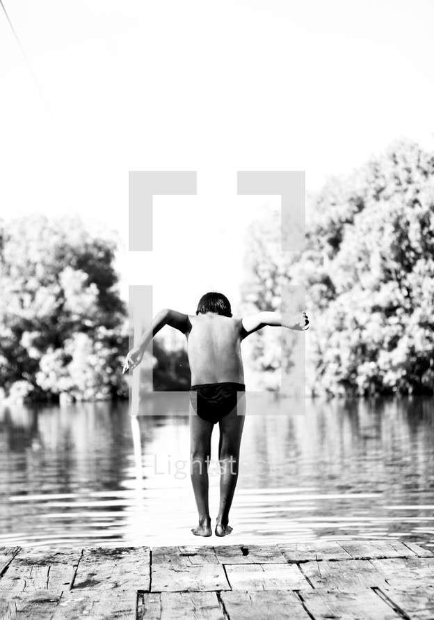Boy jumping off deck into river