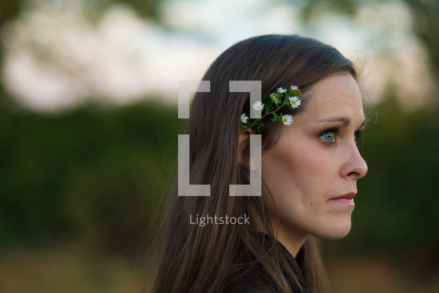 profile shot of woman with flowers behind her ear