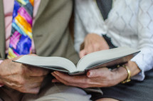 an elderly couple reading a Bible together