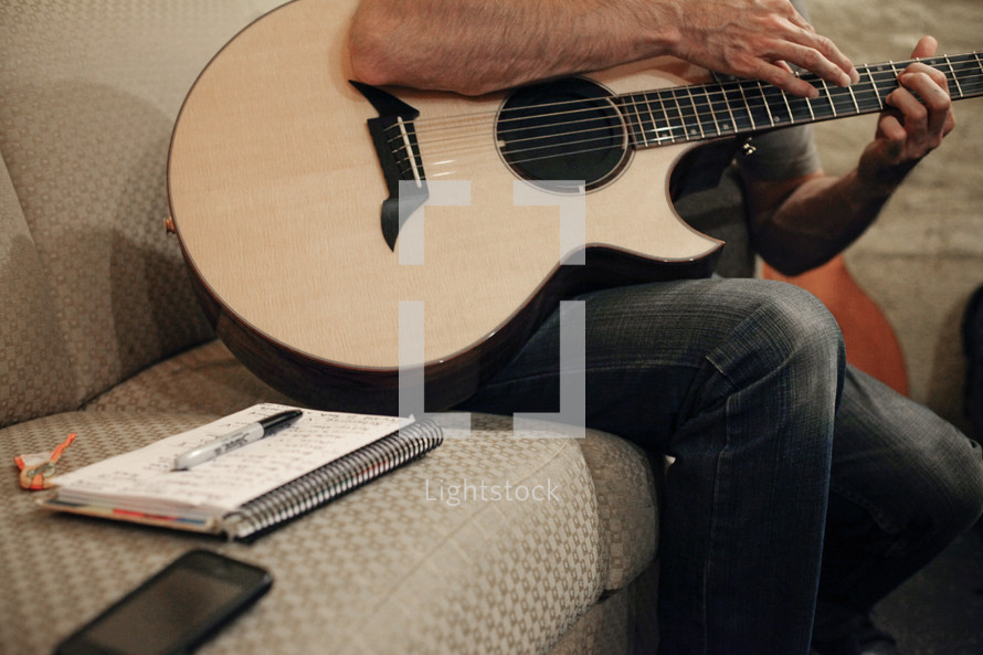 torso of a man sitting and playing a guitar