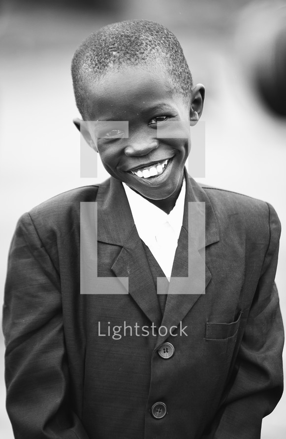 Smiling boy wearing a suit.