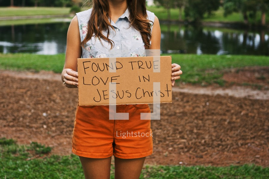 Woman holding a sign with the words FOUND LOVE IN JESUS CHRIST