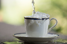 Water being poured and overflowing from a tea cup and saucer.