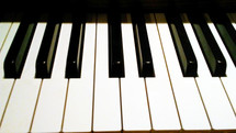 The Ivory black and white keys of a piano from the angle of a piano player or pianist.