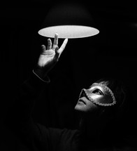 a woman in a mask looking up at a light