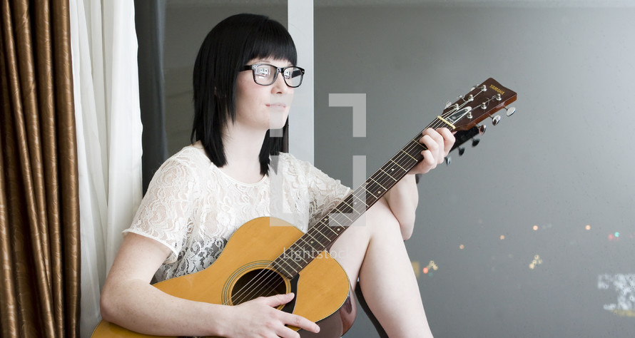 Guitarrista; hipster woman with guitar and glasses sitting by a window.