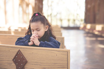 a little girl praying in church pews