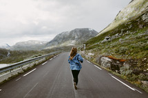 a woman jogging in the middle of a road