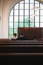 bride and groom sitting in church pews