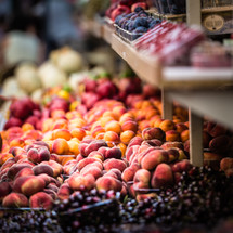 peaches, grapes, plums, and berries at a farmers market