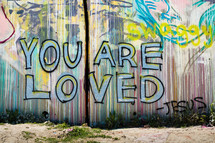 "A grafitti painting on a wall reading, ""You are loved. Jesus."""