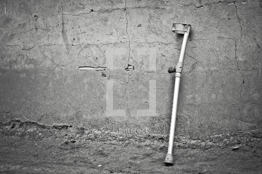 A crutch resting against a concrete wall