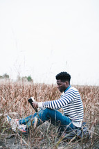 a African-American man sitting in a field reading a Bible