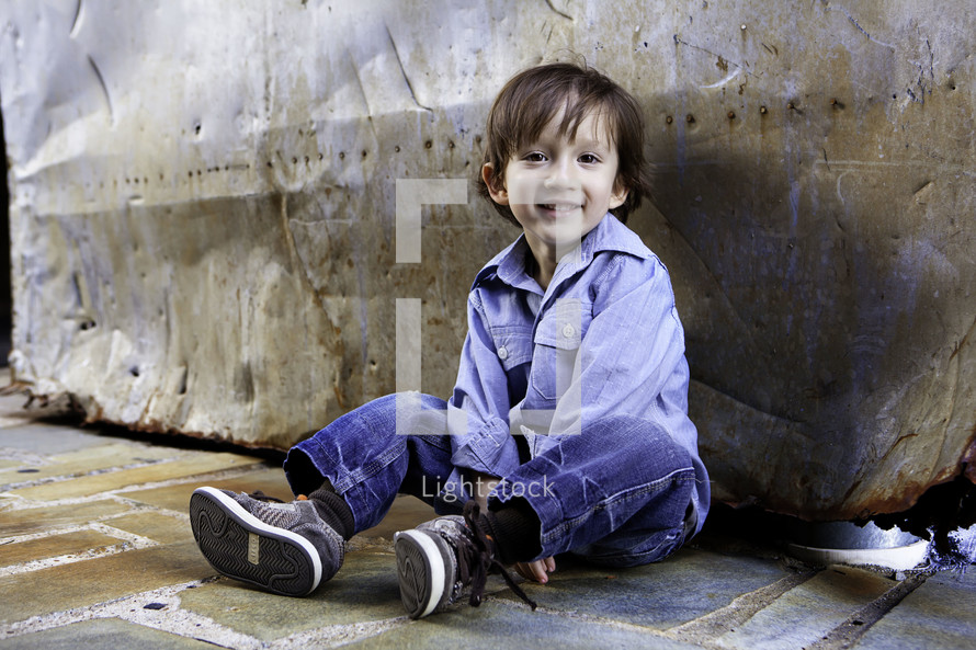 boy sitting on stone floor against rock