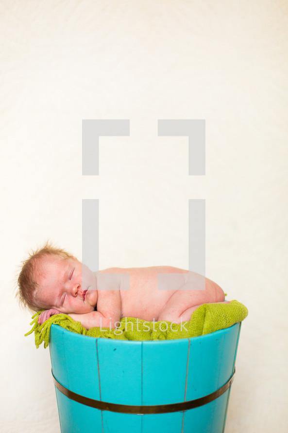 Newborn baby sleeping on top of blanket stuffed in bucket