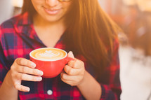 a woman in a plaid shirt holding a latte