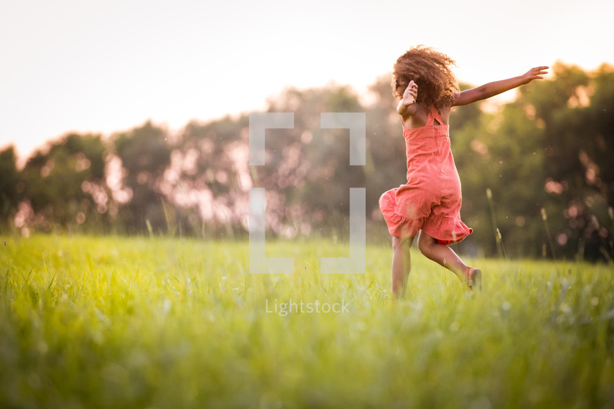 an excited girl running in grass