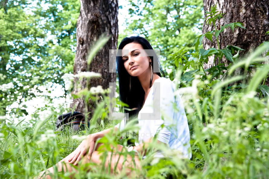 a model sitting in a forest