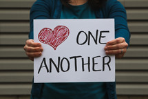 A woman holding a sign that says love one another.