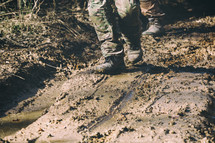Brown military boots on mud and puddle