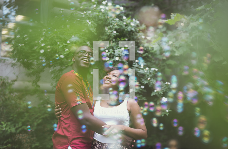 An African American couple in love looking up at bubbles