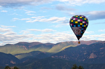 Hot air balloon flying over the mountains of Colorado in the morning light
