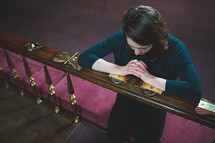 a woman praying at an altar