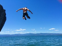 a man jumping off a cliff into the ocean