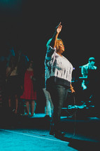 woman with raised hand in worship at a worship service