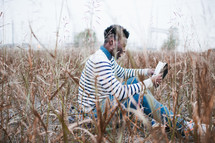 African-American man sitting in a field reading a Bible
