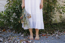 barefoot woman holding a bouquet of flowers