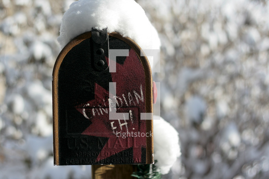 """Red mailbox in the snow with """"Canadian Eh!"""" written on front."""
