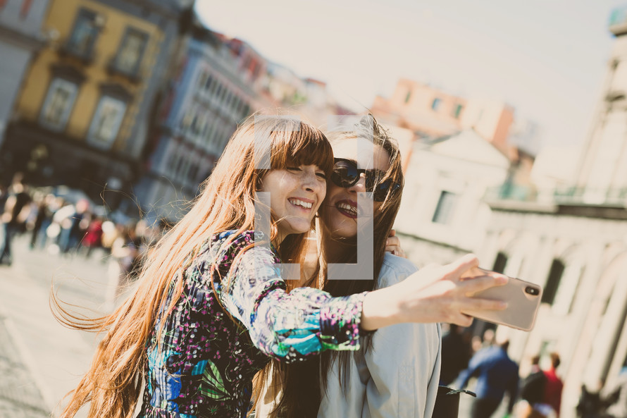 Two young adults take a selfie in Piazza del Plebiscito in Naples.