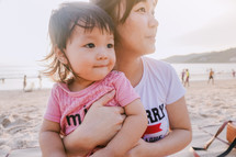 mother holding her infant daughter on a beach