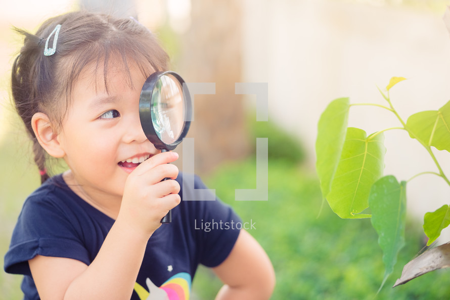 child looking at leaves through a magnifying glass