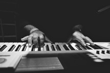 Hands playing a keyboard.