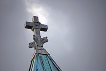 A break in the storm clouds highlights the decorative cross atop the steeple of St. Michael's Basilica in Pensacola FL.