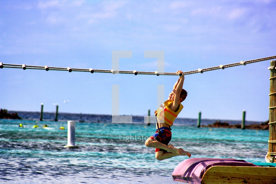 Boy hanging from over-head rope ladder off pier in ocean.