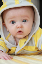 face of an infant boy in a hoodie