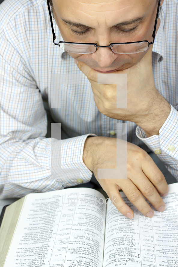 a man in glasses reading a Bible