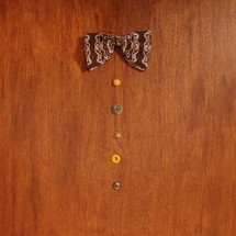A bowtie and buttons lined up on a brown table.