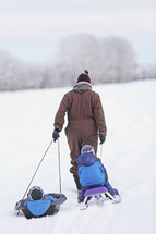 Pulling two children on sleds in the snow