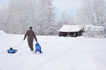 A man pulls two children on sleds through the snow.