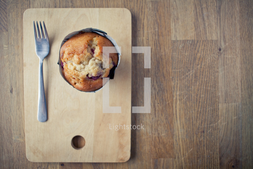 a muffin and a fork on a plate