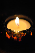 Lighted votive candle in glass holder