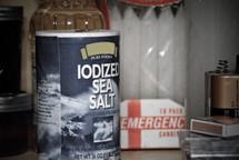 The cupboard shelf holds the survival basics: light, salt, oil--symbols of Christian life.