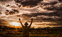 man standing with his hands raised in worship at sunset